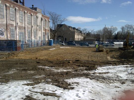 Heavy equipment grading the exposed ground at the town square site