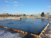 Beginning of an outdoor natural ice rink with some flooding done but not a complete surface.