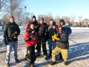 Photo of seven volunteer rink flooders with their tools, ready to build the rink