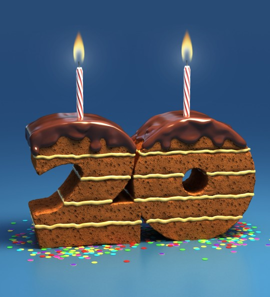 Picture of chocolate cake in the shape of the number 20 with two candles on top