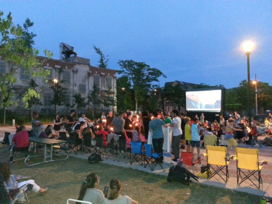 Photo of crowd at Sorauren Park outdoor movie, including people holding sparklers for a marriage proposal