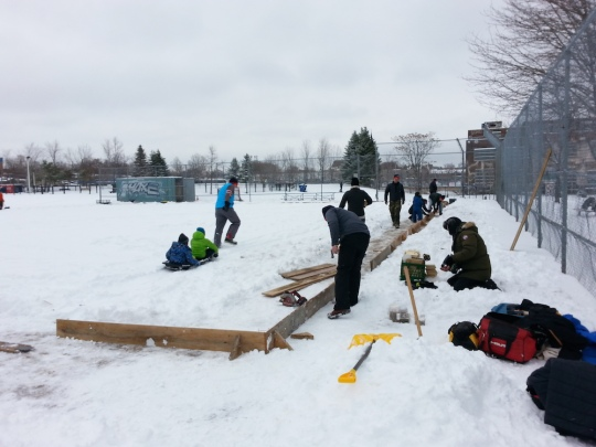 Photo of volunteers setting up the boards for the outdoor rink. Lots of snow.
