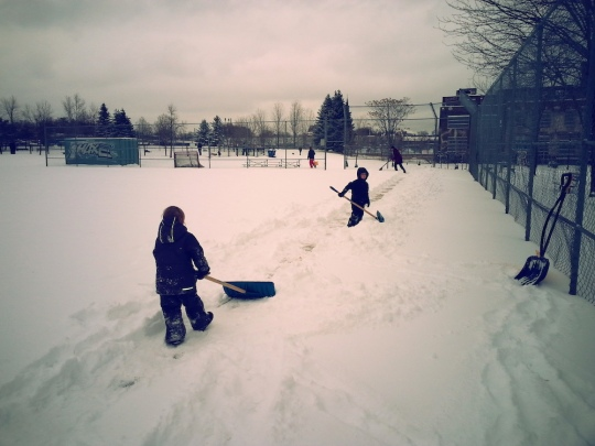 Children with shovels prepare a path in the snow that marks where the rink boards will be installed