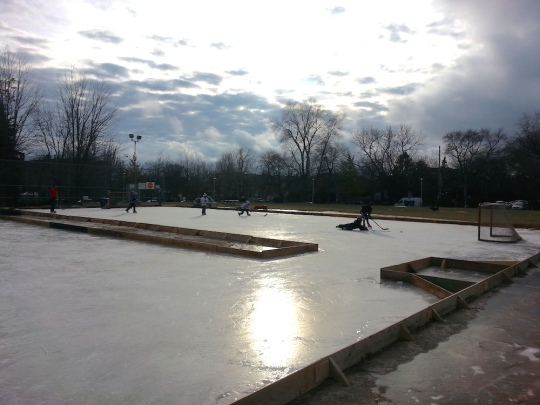 Photo of the natural ice rink with the sun's glare and hockey players in the background