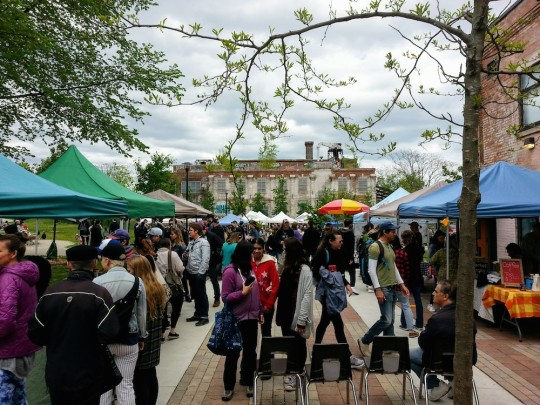 Photo of farmers market outdoors with colour tents at each vendor's booth, and crowds of shoppers.