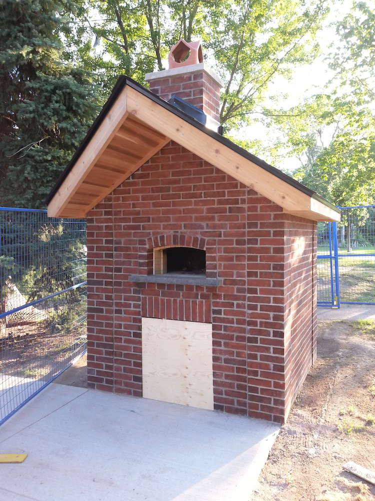 Photo of brick bake oven with peaked roof and chimney