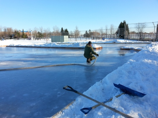 Photo of man on natural ice rink holding a hose spraying water. Blue sky, and snow around the rink boards.