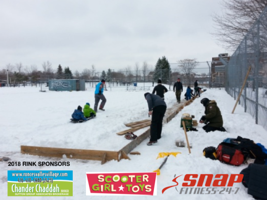 Photo of volunteers installing rink boards on snowy baseball diamond