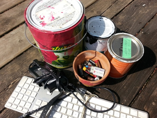 Photo of old paint cans, batteries and electronics for disposal.