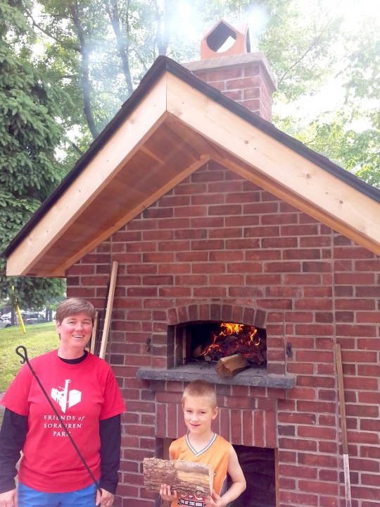 Mother and young son, both volunteers with Friends of Sorauren Park, in front of the brick oven, with a fire blazing inside and smoke coming from the chimney