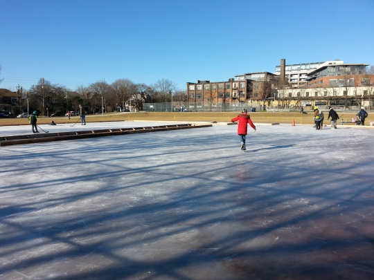 skaters on a two-pad natural ice rink under blue skies