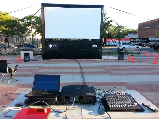 Photo of inflated outdoor movie screen on the Sorauren Town Square, with the projection table in the foreground.