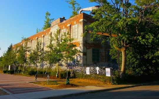 Photo of old brick linseed factory, bright sunlight on the west wall