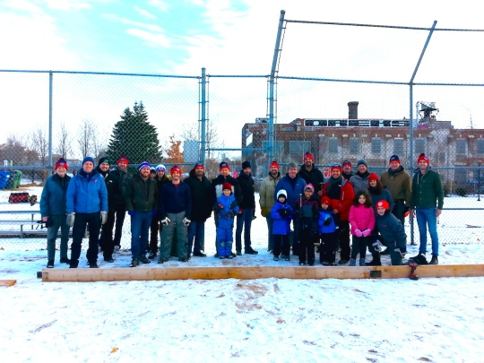 27 adults and children pose on the snowy baseball diamond where they are erecting the boards for the Sorauren Rink