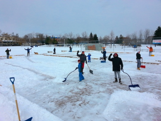 A dozen volunteers, young and old, shovel the Sorauren ice rink after a storm, waving to the camera.