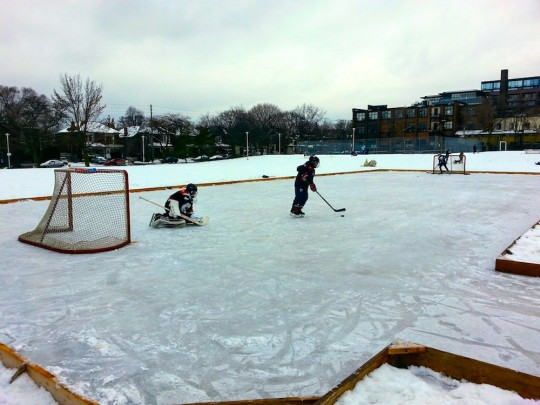 Kids playing shinny hockey on natural ice rink at Sorauren Park