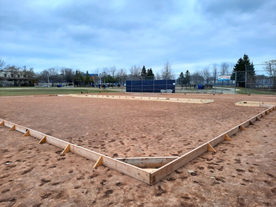 Photo of the newly erected rink boards, the 2 x 8s that mark the perimeter of the rink, placed on the baseball diamond at Sorauren Park.