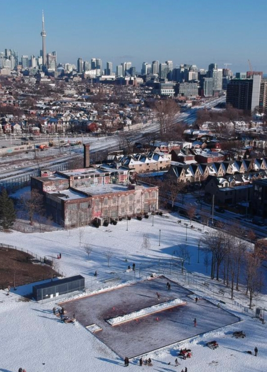 Drone shot showing Sorauren Rink, snow-covered park and town square, the linseed building and Toronto skyline in the background including CN Tower