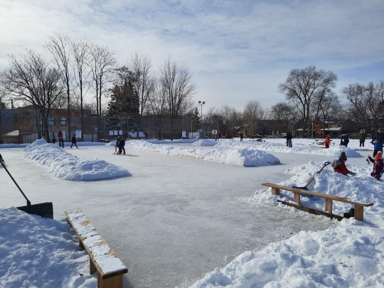 View of the frozen natural ice rink surrounded by snow banks and showing the snow banks down the middle that turned the rink into a skating trail, a special design for 2021 COVID season. Blue skies with clouds.