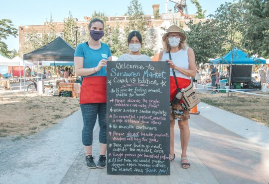 Three volunteers with the Farmers' Market, wearing their face masks, stand behind a sign outlining the COVID-19 rules for attending the market, taken at the 2020 market outdoors on the Sorauren Town Square.